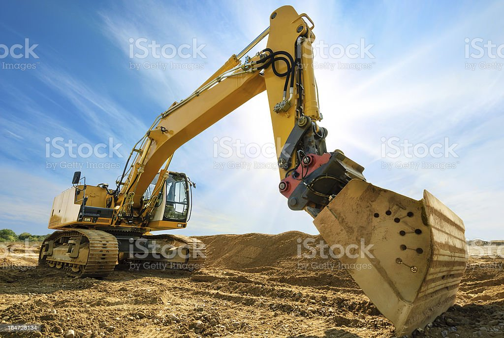 Big excavator in front of the blue sky stock photo