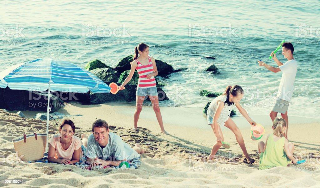 Big family resting on beach stock photo