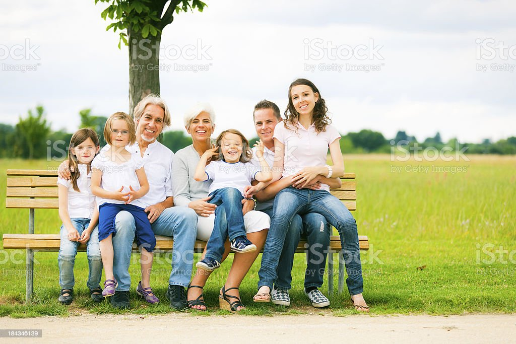 big family sitting on a bench royalty-free stock photo
