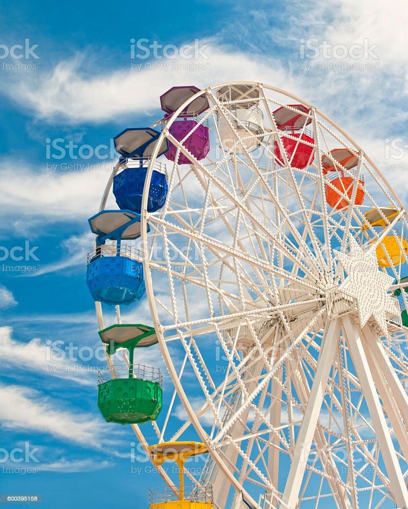 big ferris wheel with colourful gondolas against blue sky stock photo