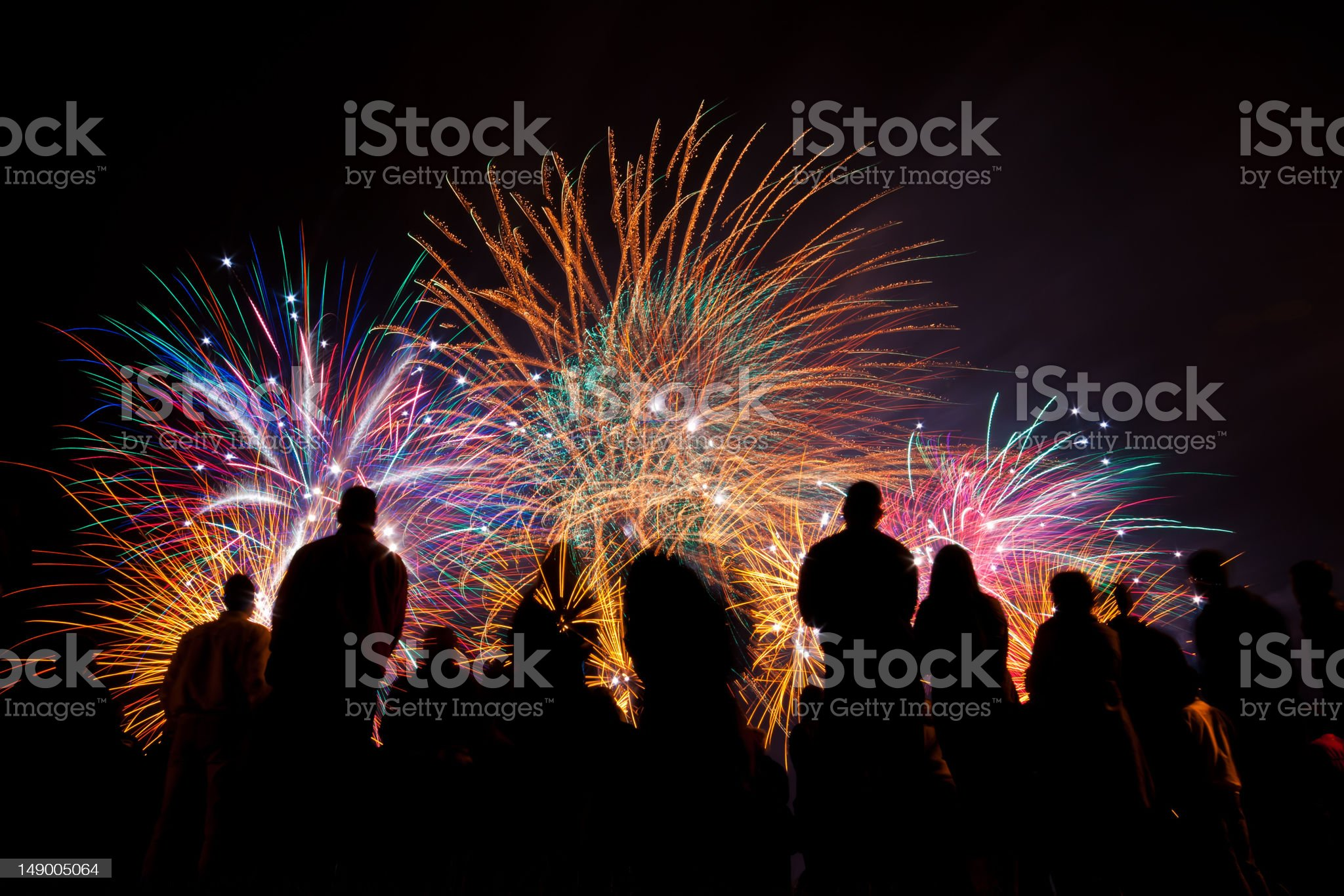 Big fireworks with silhouetted people in the foreground watching royalty-free stock photo