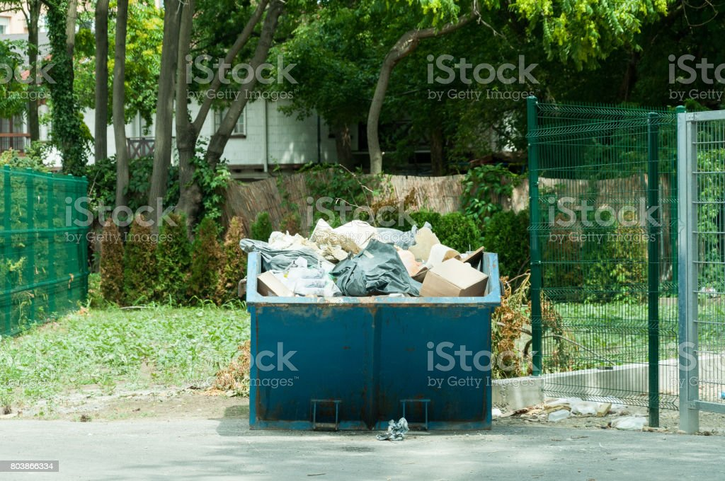 Big garbage container on the street full of litter. Garbage in the city. stock photo