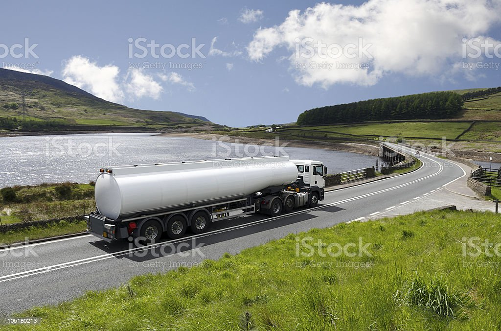 Big gas tanker truck on scenic highway with lake stock photo