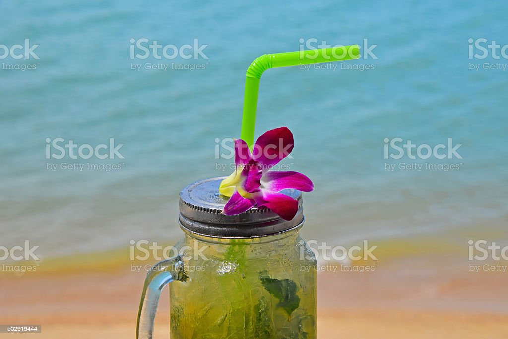 Big glass of mojito with orchid flower on beach royalty-free stock photo
