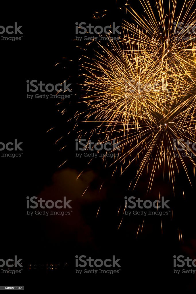 Big gold fireworks in the sky over a lake stock photo