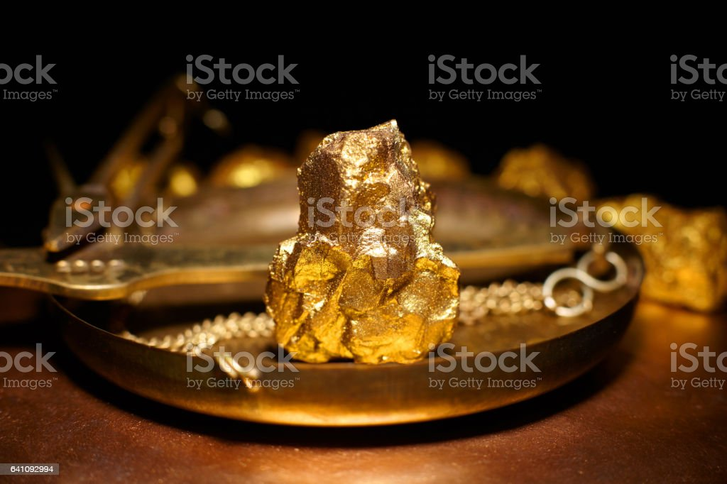 big gold nugget and scales copper stock photo