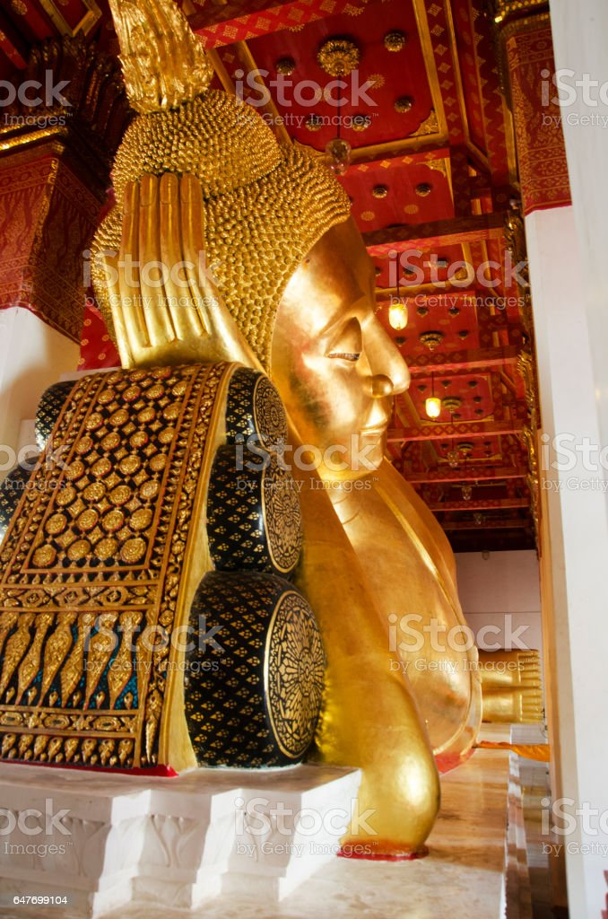 Big golden reclining buddha statue in ubosot stock photo