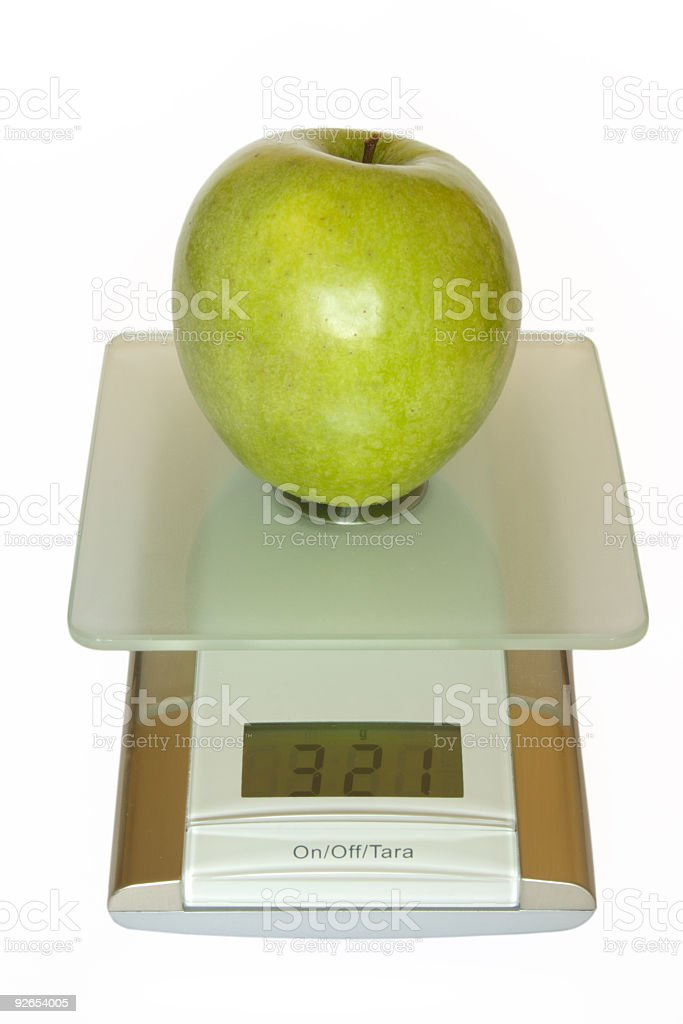 Big green apple on electronic kitchen scales royalty-free stock photo