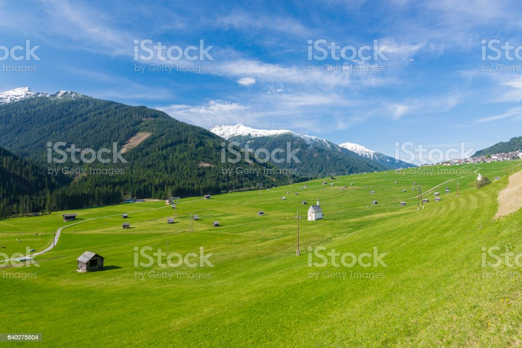 Big green meadow with pastoral houses stock photo