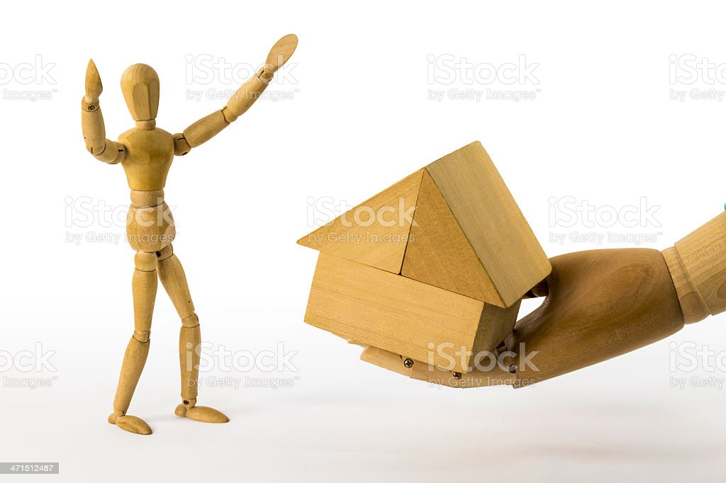 Big hand gives a house to dummy man royalty-free stock photo