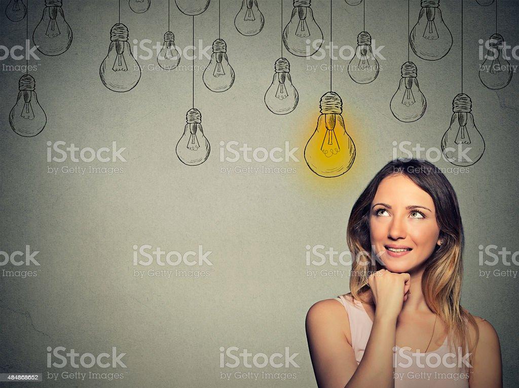 Big idea. Happy smart girl with solution lightbulb above head stock photo