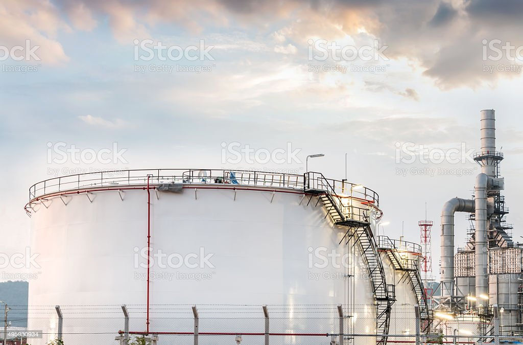Big Industrial oil tanks in a refinery with treatment pond stock photo