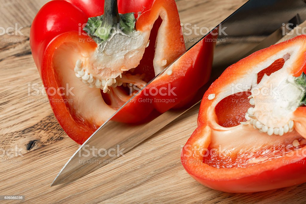 Big kitchen knife cut a bell pepper on two parts stock photo