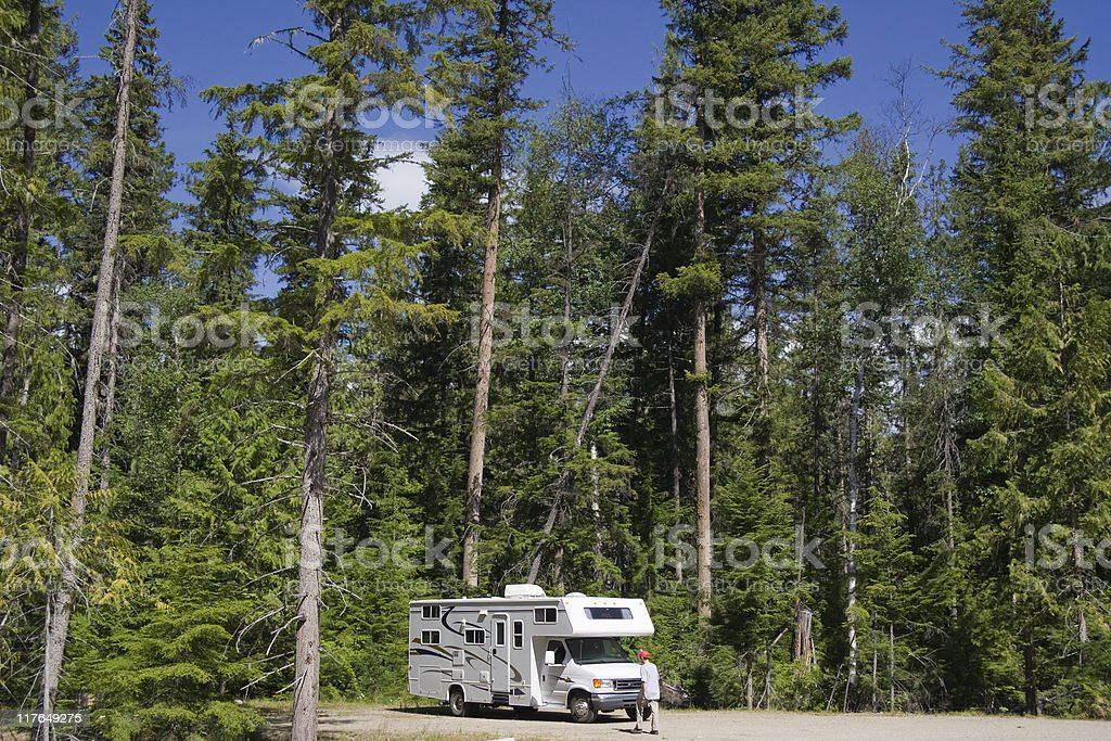 Big Motorhome with owner in the woods royalty-free stock photo