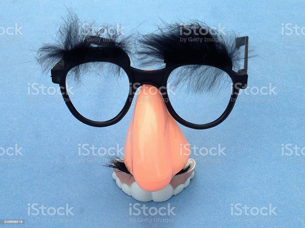 Big nose, bushy eyebrows and funny teeth face around eyeglasses stock photo