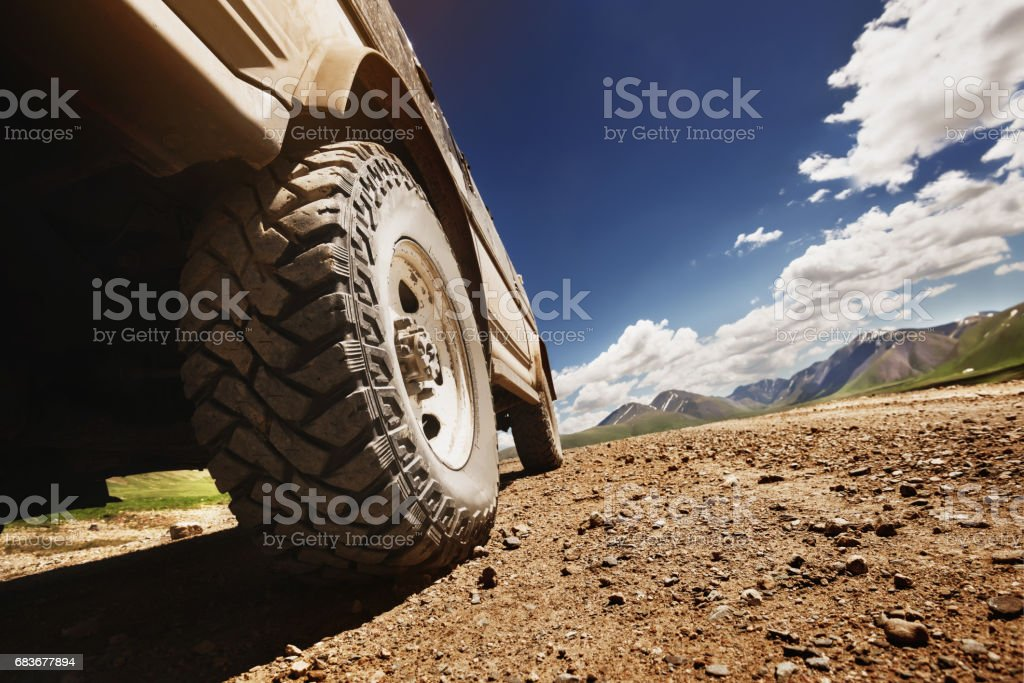 Big offroad car wheel on country road stock photo
