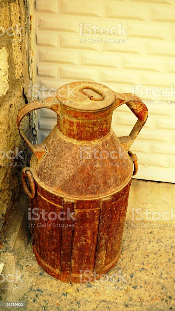 big old metal milk churn, on brick background stock photo