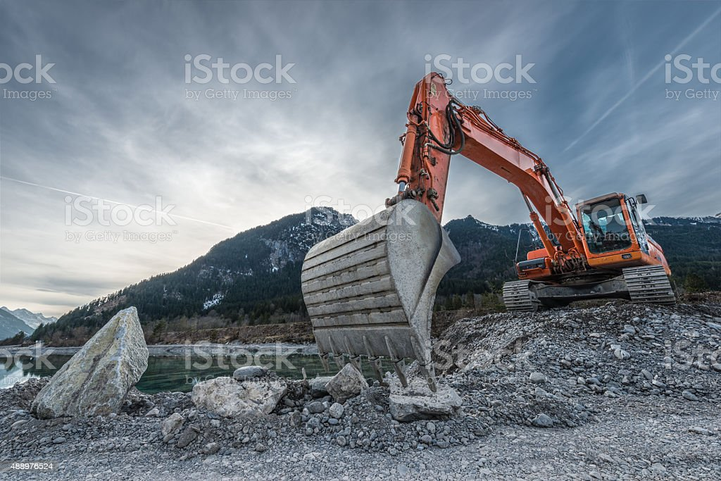 big orange digger on gravel heap with big shovel stock photo