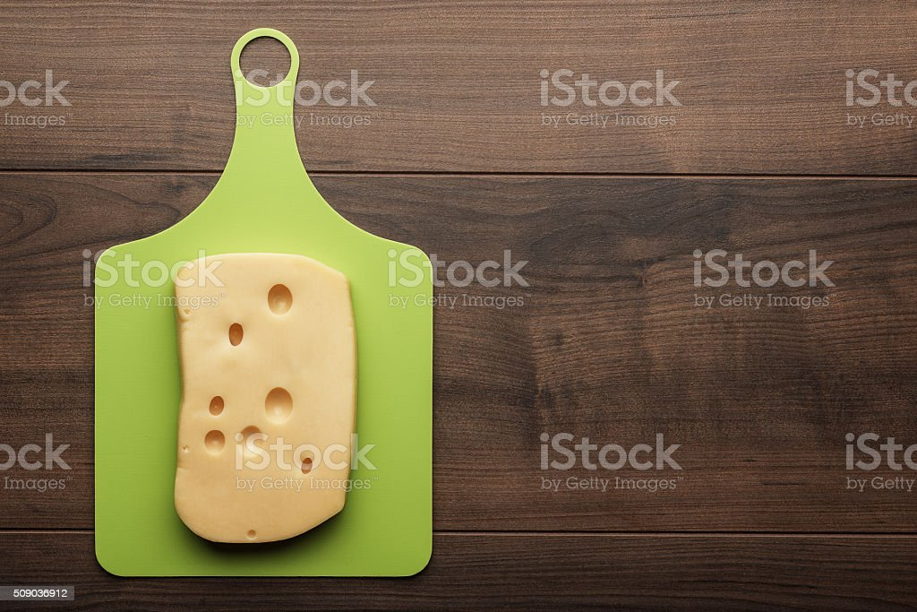 big pieces of cheese on the cutting board stock photo