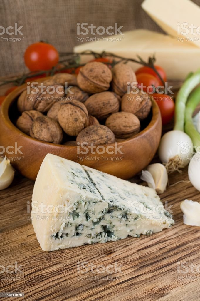 Big portion of niva cheese in front of various vegetable stock photo