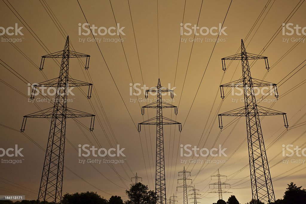 Big power poles connected with power lines at night stock photo