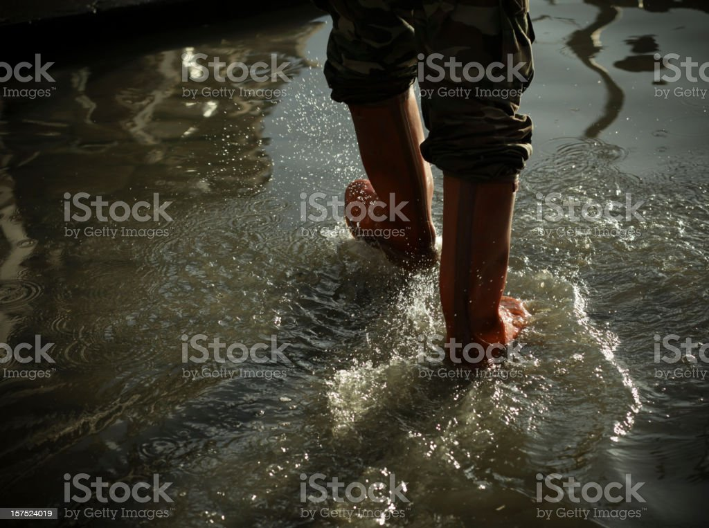 Big puddle of water being walked in with red rubber boots stock photo
