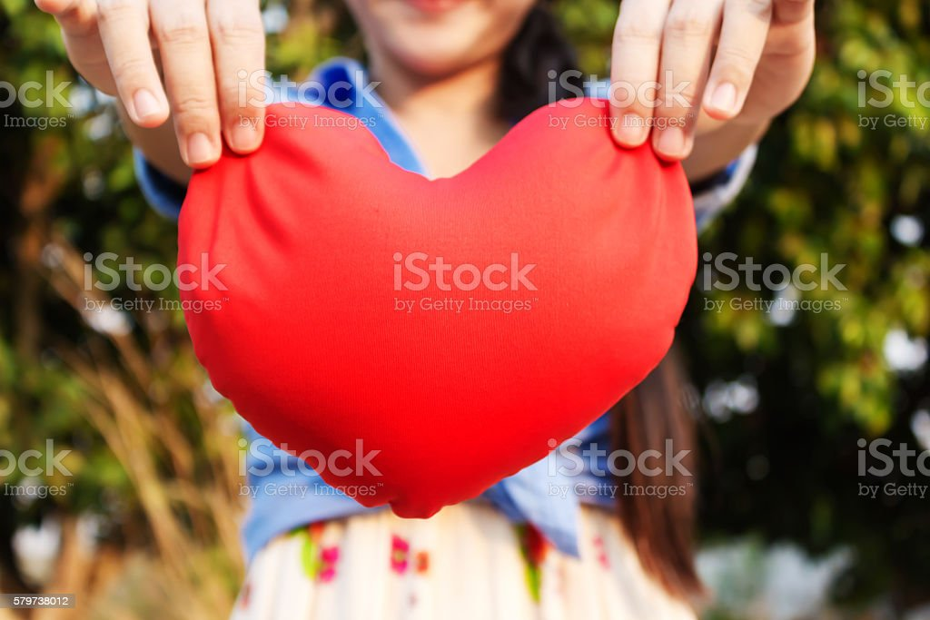 Big red heart and background of girl or women hands stock photo