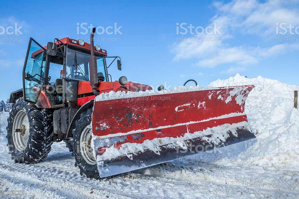 Big red snow plow on snowy road stock photo
