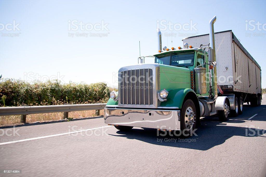 Big rig attractive green semi truck with bulk trailer stock photo