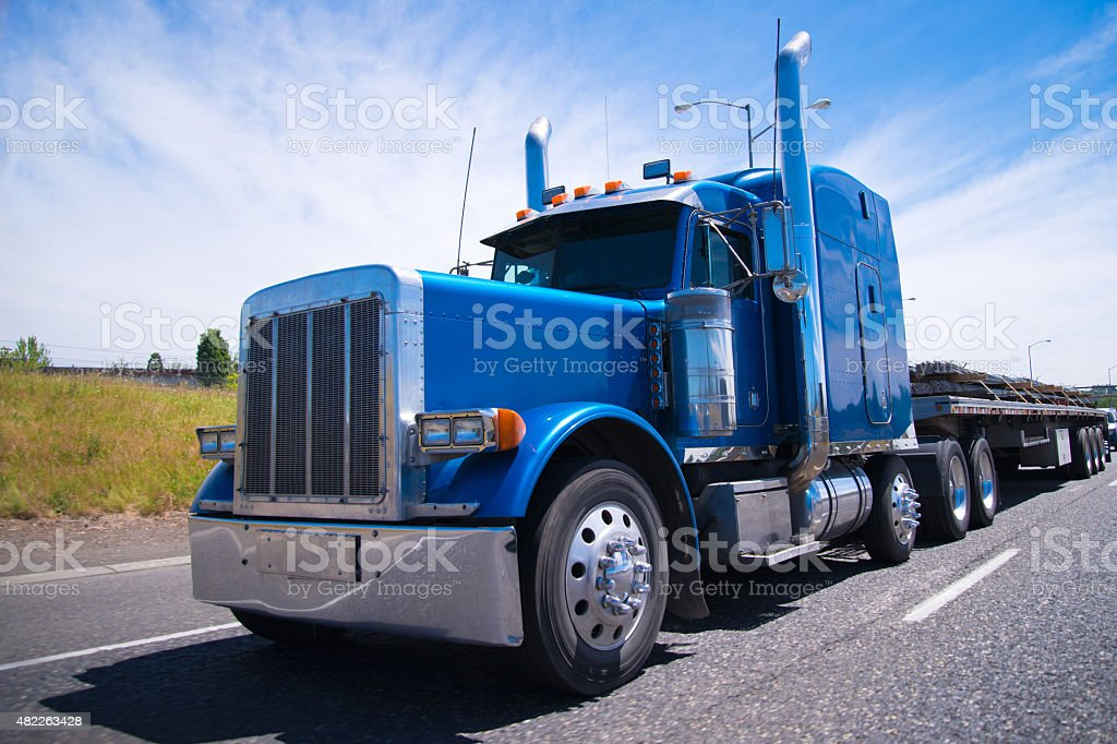 Big rig semi truck blue wolf of roads stock photo