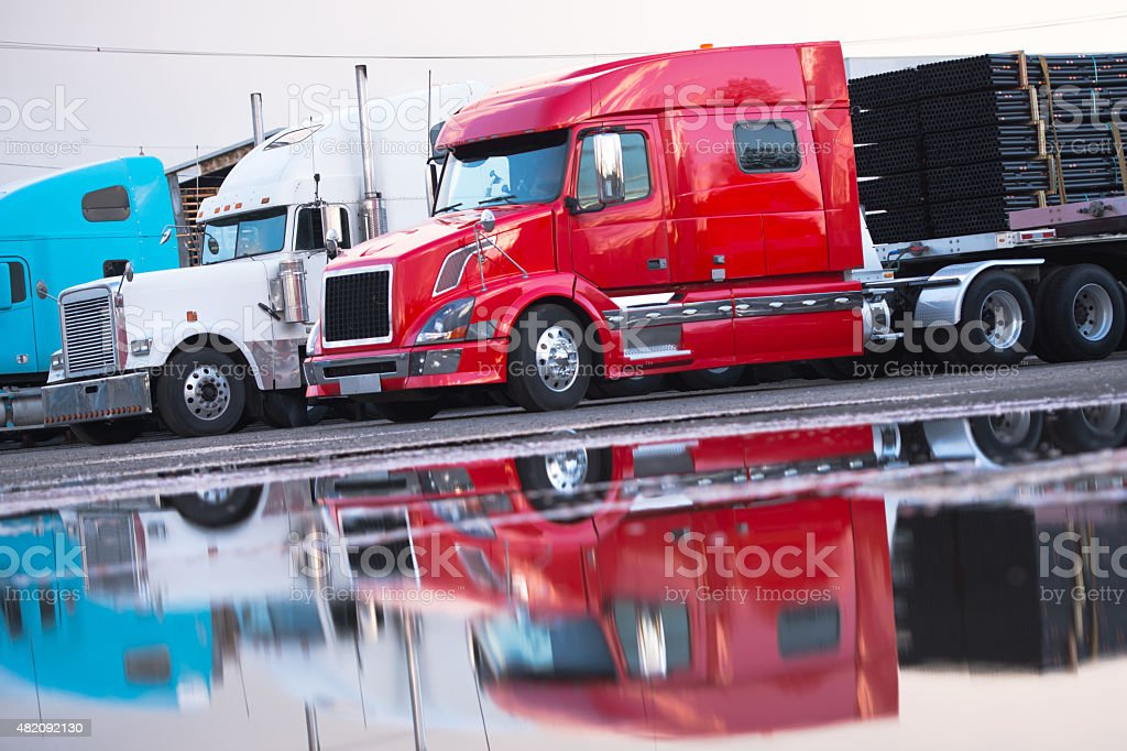 Big rig semi truck flat bed trailer cargo parking lot stock photo