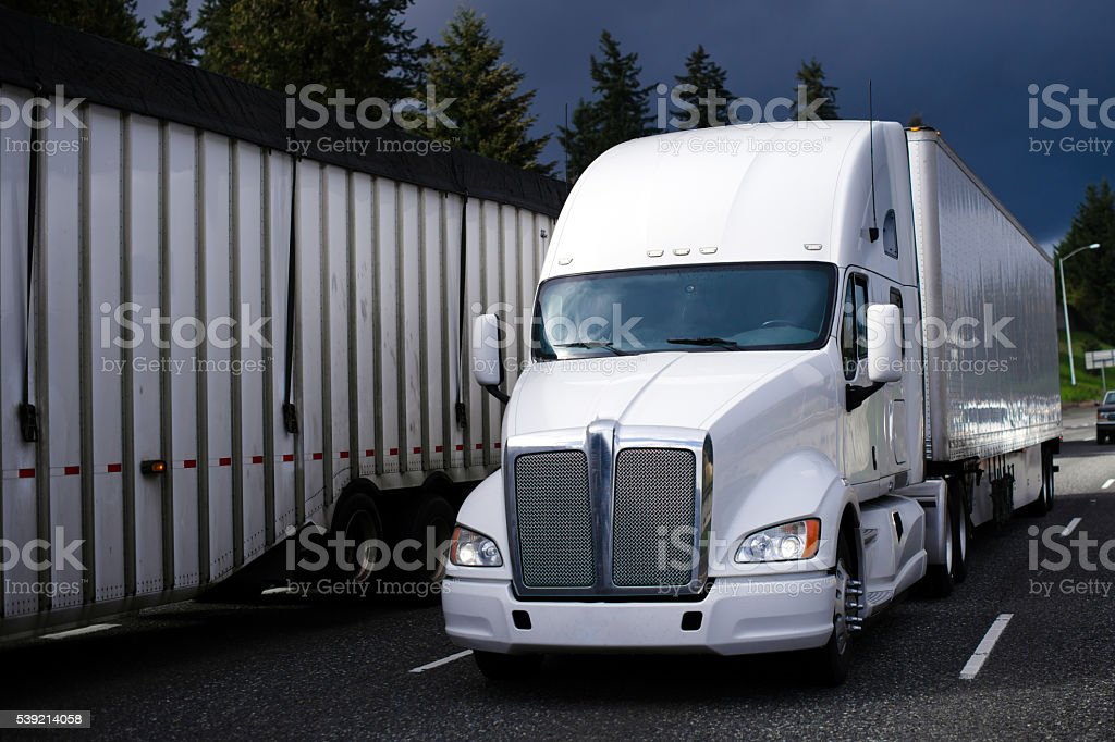 Big rig semi truck on highway with stormy sky stock photo