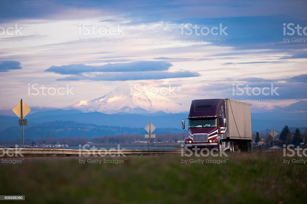 Big rig semi truck on straight road with snow mount stock photo