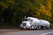 Big rig semi truck two tank trailers on autumn road