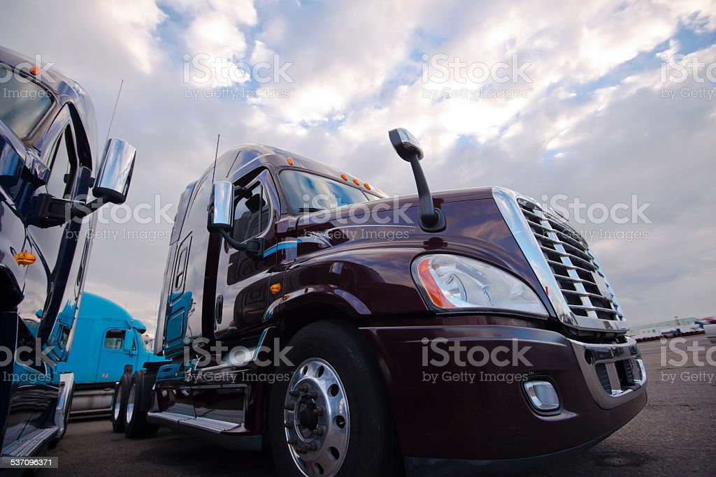 Big Rig semi trucks standing on trakstope background cloudy sky stock photo