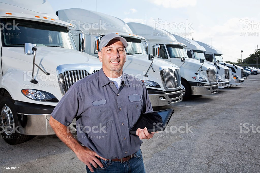 A truck driver is standing in a large parking lot in front of several...