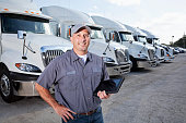 Big rig trucks behind man holding tablet