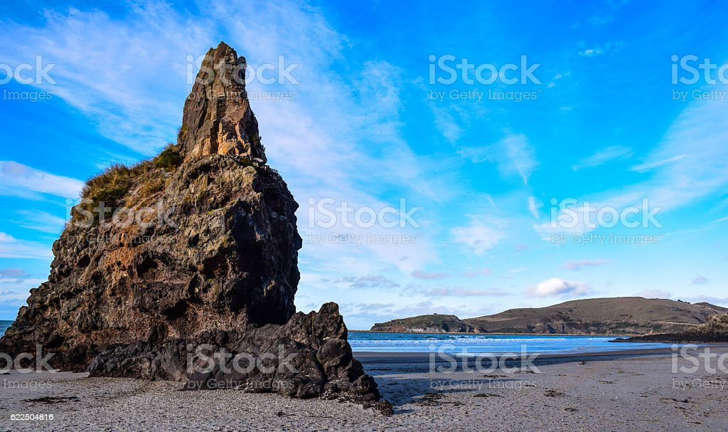 Big rock standing on a quiet beach of New Zealand royalty-free stock photo