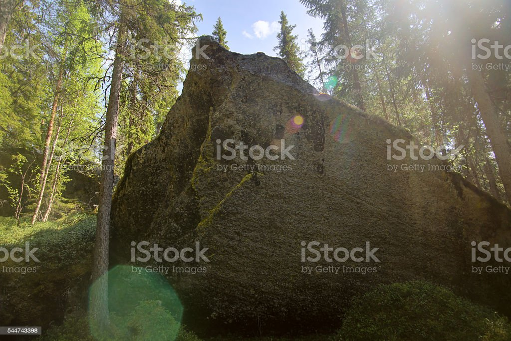 Big rock with lens flares in Swedish forest stock photo