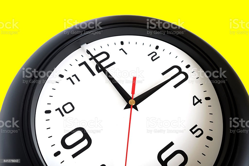 Big round wall clock isolated on yellow close-up stock photo