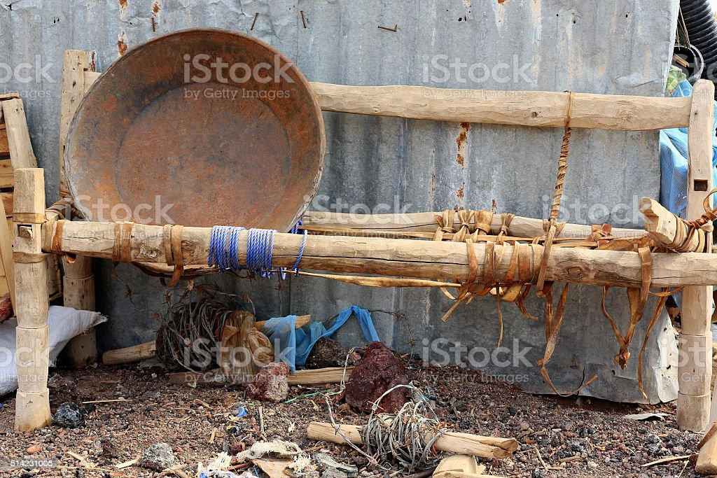 Big rusty pan on rustic wood-leather straps coach. Afrera-Ethiopia. 0173 stock photo