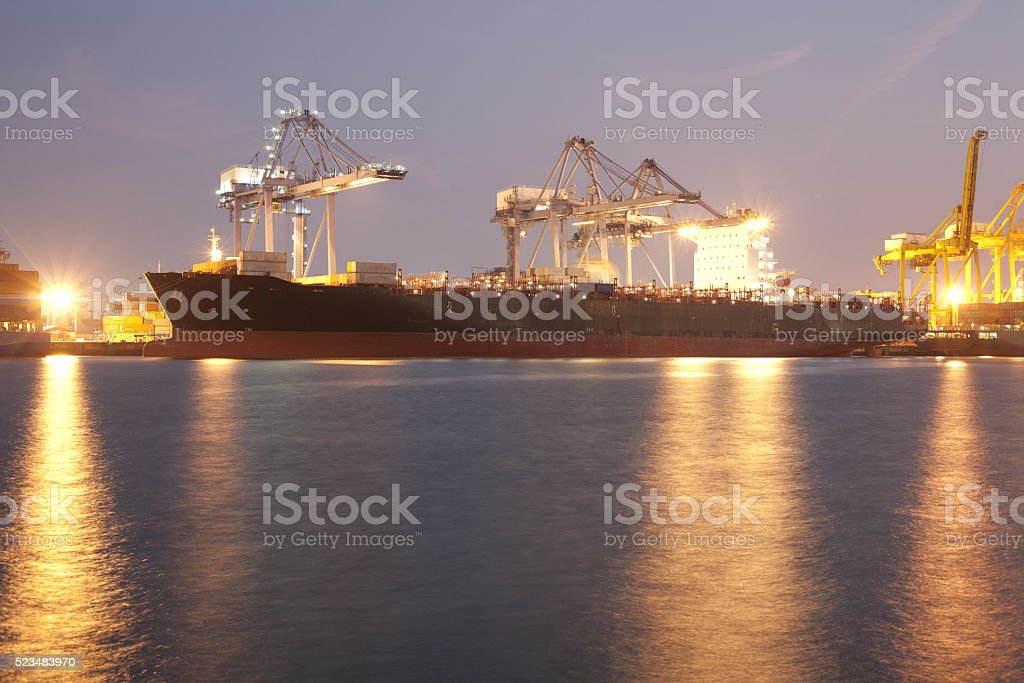 Big ship in harbor using cranes loading containers in night time stock photo