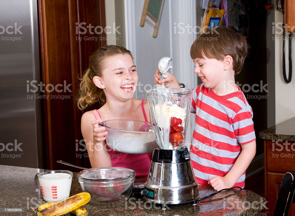 Big Sister and Little Brother Making Milkshakes royalty-free stock photo