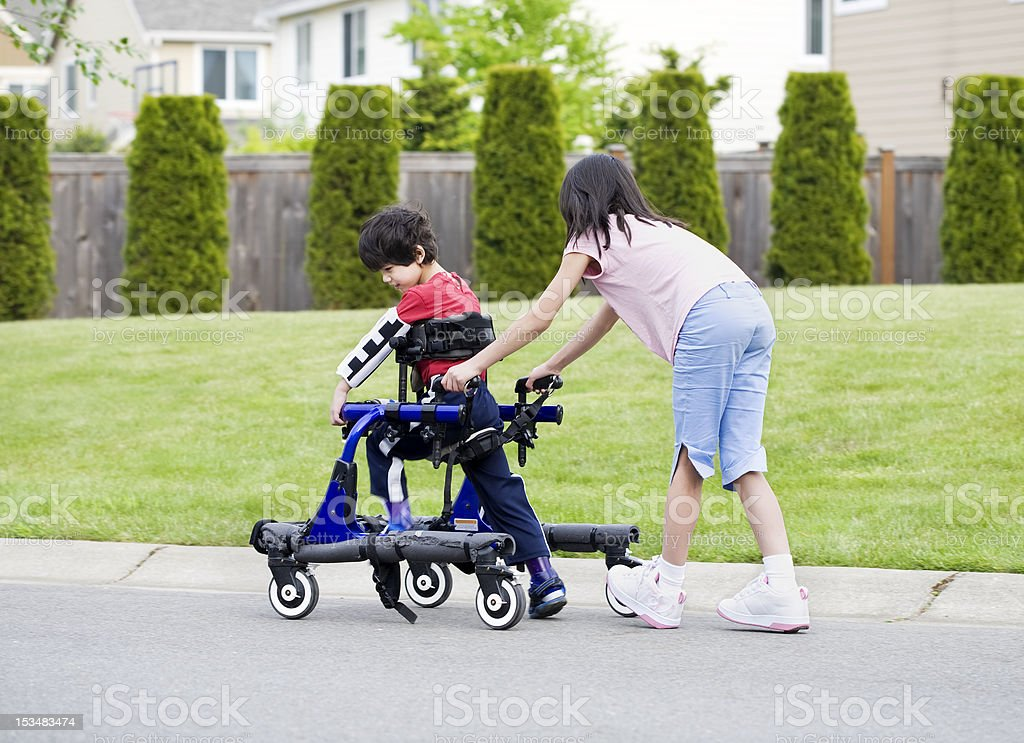 Big sister helping younger disabled brother in walker royalty-free stock photo