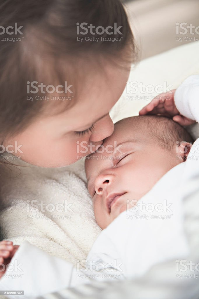 Big sister kissing her newborn brother stock photo