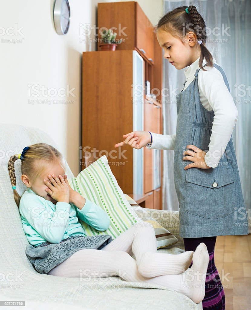 big sister preaching little one stock photo