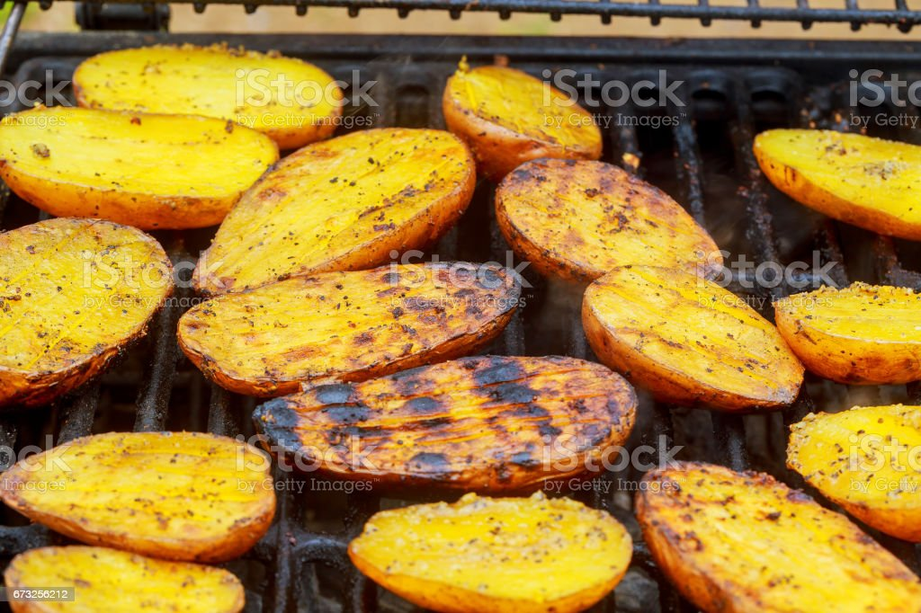 Big Slice Of Village-Style Potatoes On Hot BBQ Charcoal Grill. Flames of Fire In The Background. stock photo
