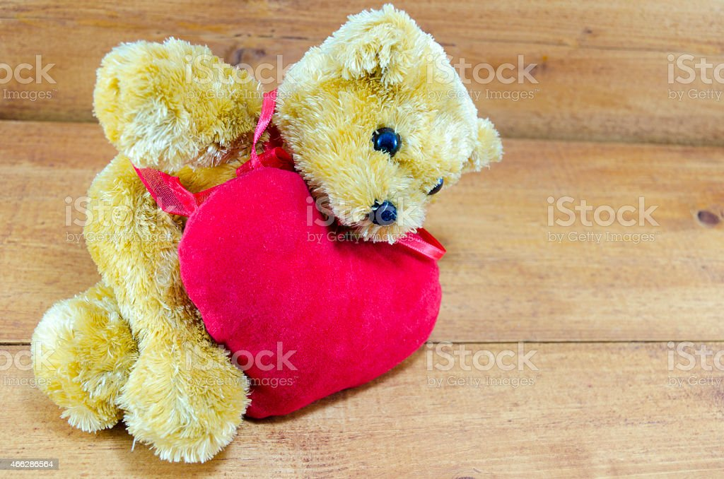 Big teddy bear lying on a red heart royalty-free stock photo