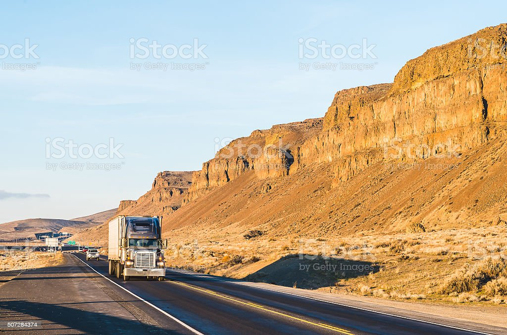 big truck driving in the sunset with mountain background. stock photo