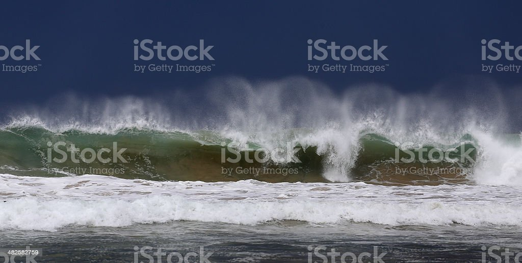 Big wave breaking close to shore, looks like a tsunami stock photo